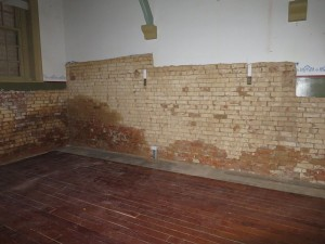 The north wall with evidence of damp penetration now exposed.